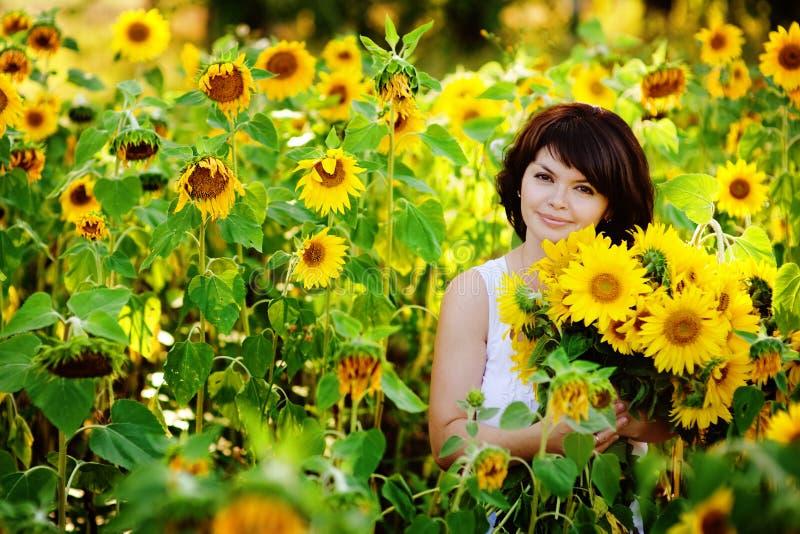 Молодая женщина с букетом солнцецветов стоковая фотография rf