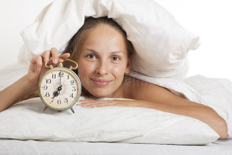 Молодая женщина с будильником на кровати на утре стоковое фото rf