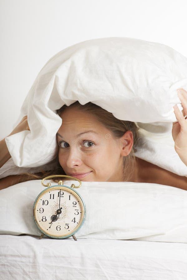 Молодая женщина с будильником на кровати на утре стоковая фотография rf