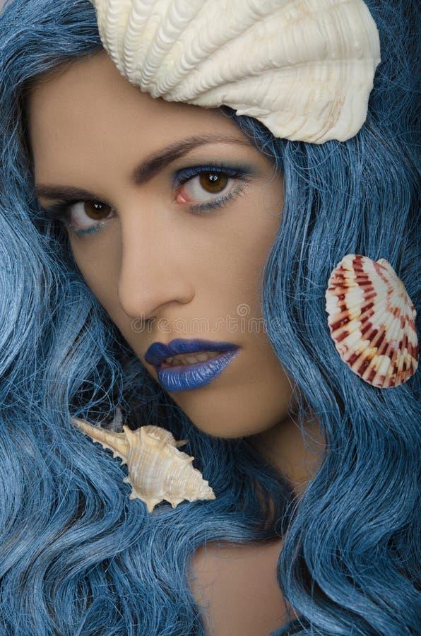 Молодая женщина с голубыми волосами и seashells стоковое изображение