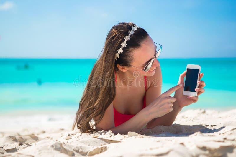Молодая женщина с ее сотовым телефоном на белом пляже стоковые фото