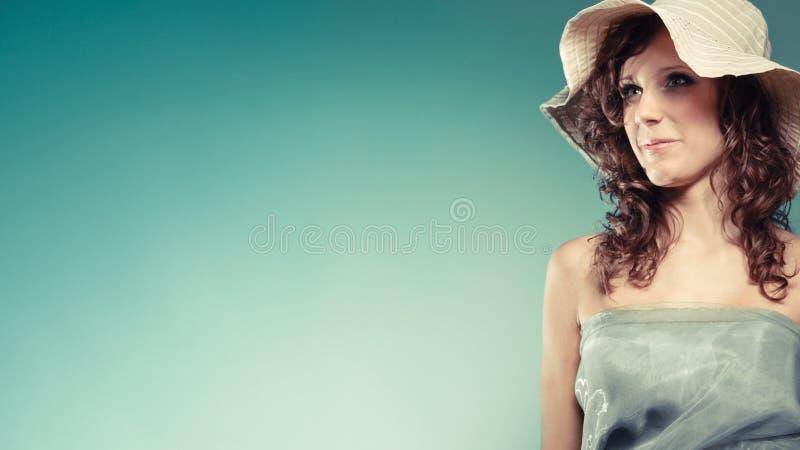 Молодая женщина с зелеными платьем и шляпой стоковое изображение