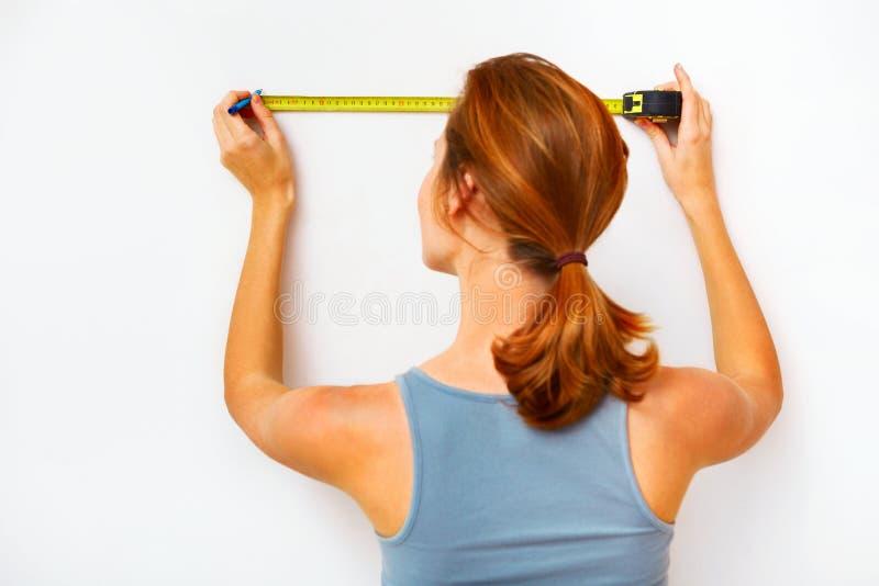 Молодая женщина с измеряя лентой стоковая фотография