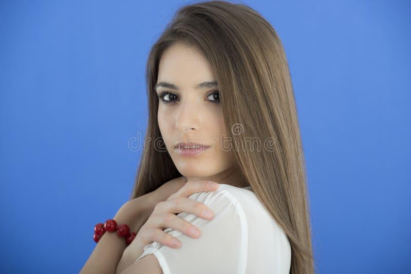 Молодая женщина с длинними волосами на голубой предпосылке стоковая фотография