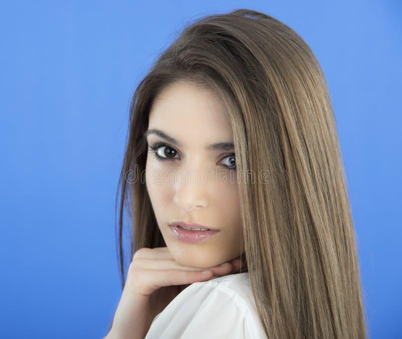 Молодая женщина с длинними волосами на голубой предпосылке стоковое изображение