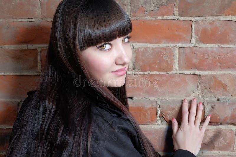 Молодая женщина с длинными коричневыми волосами смотрит назад космос экземпляра на красной кирпичной стене стоковые фото