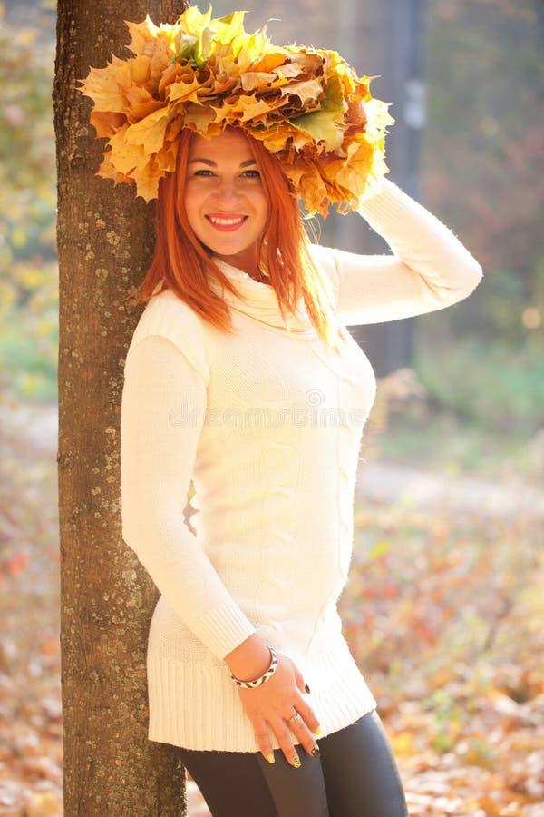 Молодая женщина с кроной кленовых листов падения стоковое изображение rf