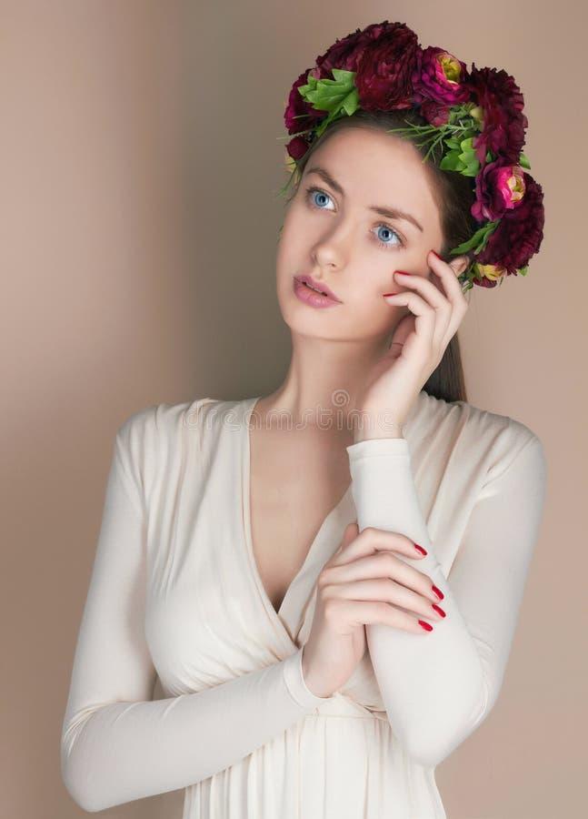Молодая женщина с кроной цветков стоковые изображения