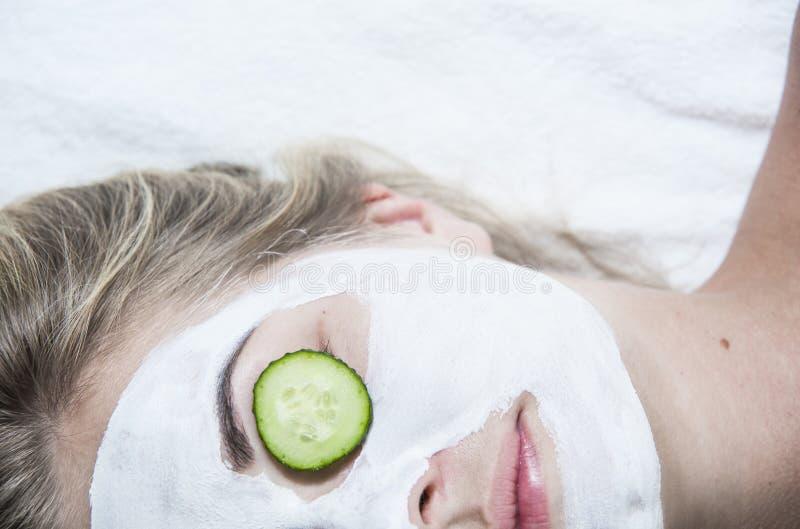 Молодая женщина с маской глины лицевой в салоне курорта стоковые фото