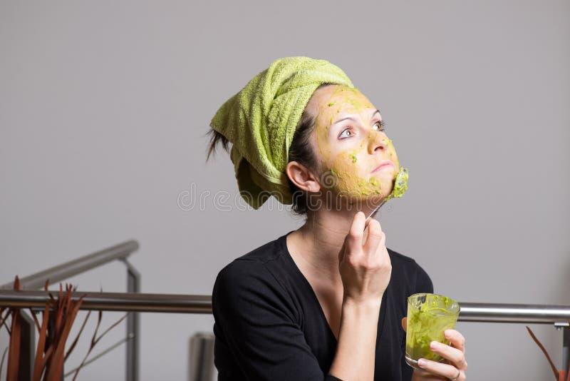 Молодая женщина с маской ухода за лицом авокадоа стоковое фото rf