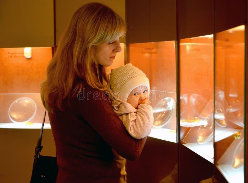 Молодая женщина с младенцем рассматривает янтарные экспонаты в mus стоковое фото