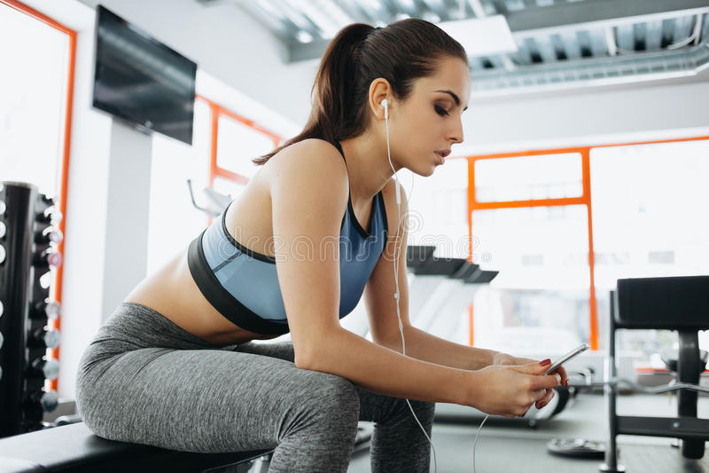 Молодая женщина с наушниками слушая к музыке после трудной разминки в спортзале стоковая фотография rf