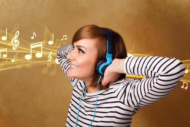 Молодая женщина с наушниками слушая к музыке стоковая фотография rf