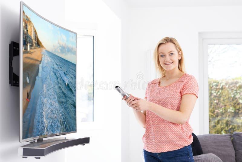 Молодая женщина с новым изогнутым телевидением экрана дома стоковая фотография rf