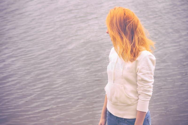 Молодая женщина с образом жизни красных волос идя внешним стоковая фотография
