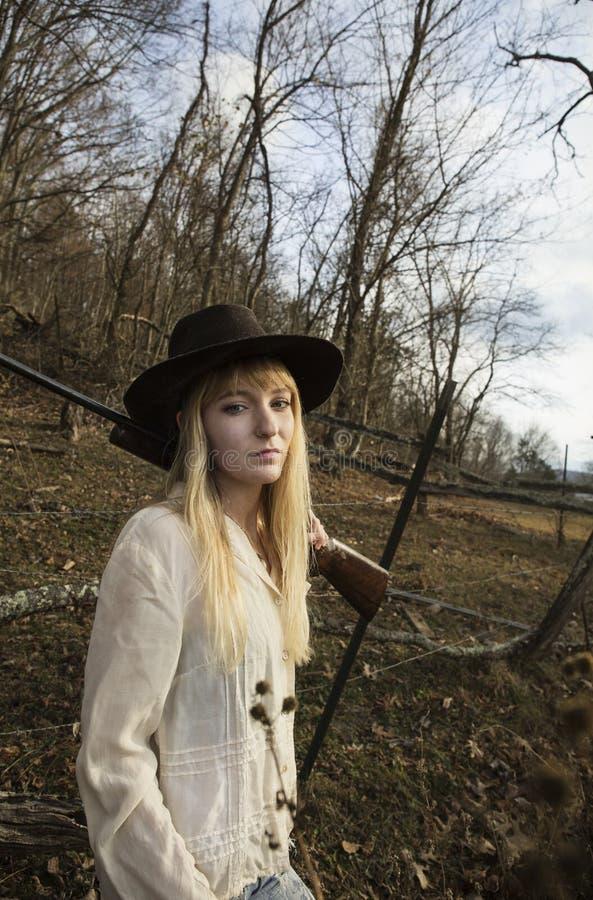 Молодая женщина с оружием над ее плечом стоковые изображения