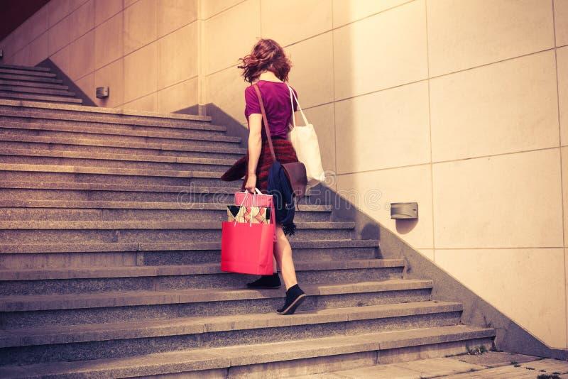 Молодая женщина с покупками идя вверх по лестницам стоковое изображение rf