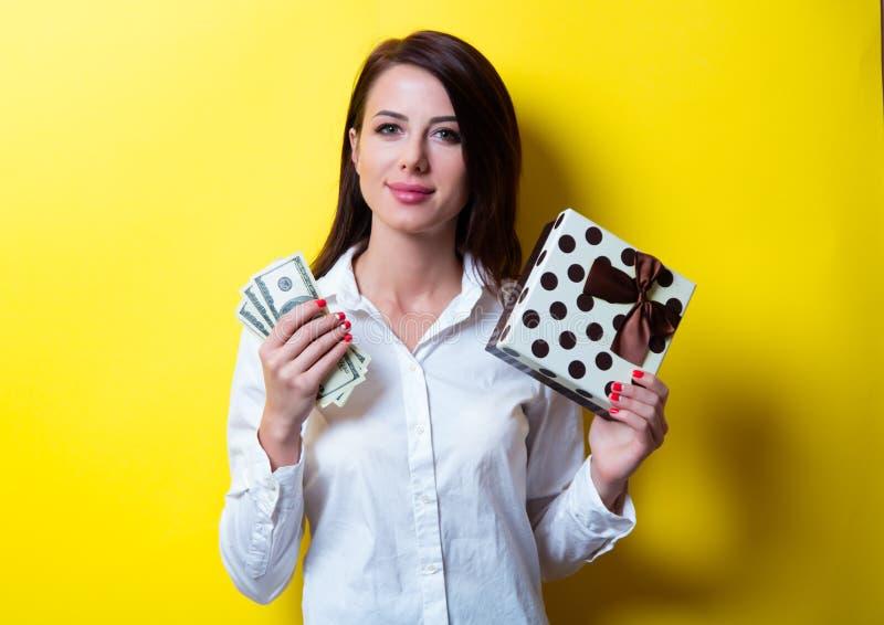 Молодая женщина с подарком и деньгами стоковое фото