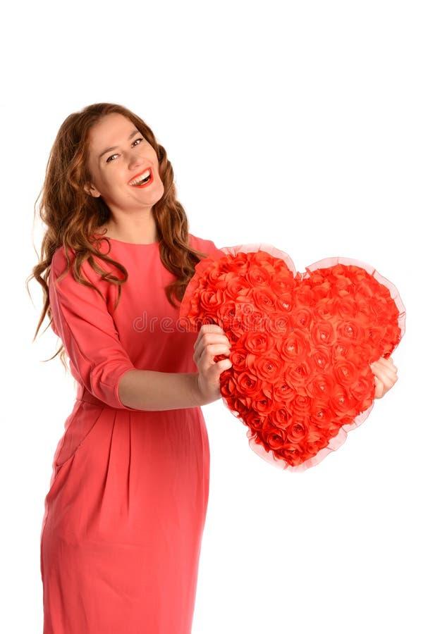 Молодая женщина с подушкой в ее руках - концепцией сердца дня валентинок Изолировано на белизне стоковые фото