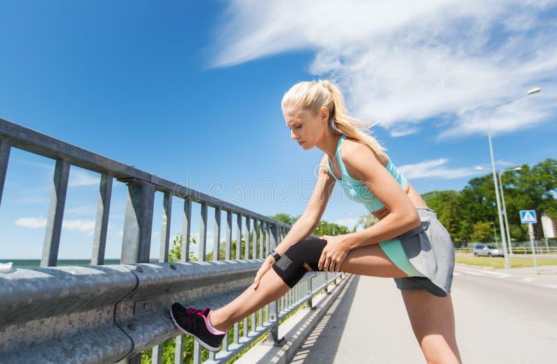 Молодая женщина с раненым коленом или ногой outdoors стоковое изображение rf