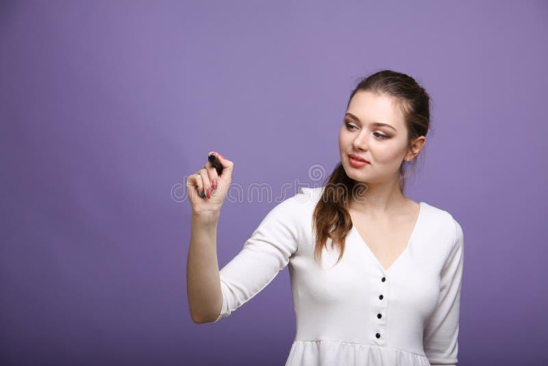 Молодая женщина с ручкой на серой предпосылке стоковое изображение rf