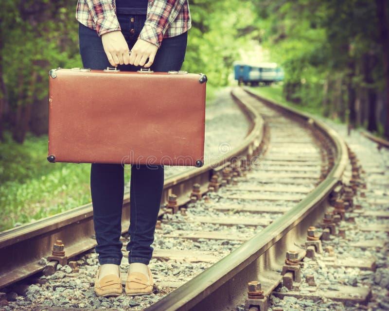 Молодая женщина с старым чемоданом на железной дороге стоковое фото rf