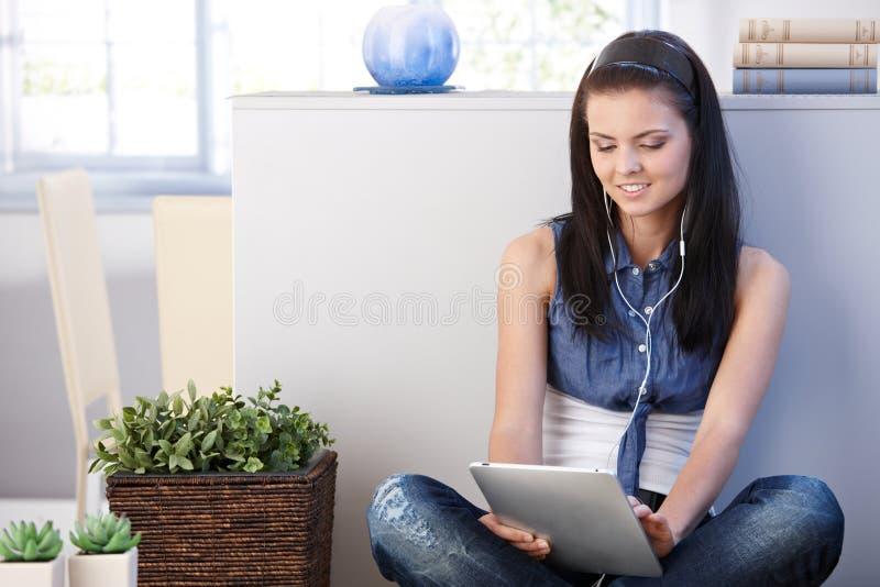 Молодая женщина с таблеткой дома усмехаясь стоковые изображения