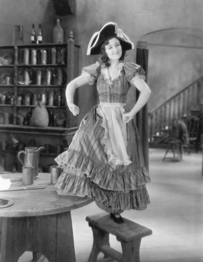 Молодая женщина с танцами шляпы пиратсва на стуле (все показанные люди более длинные живущие и никакое имущество не существует Wa стоковая фотография