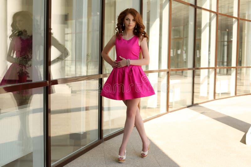 Молодая женщина с темными волосами в элегантном платье идя городом лета стоковое изображение rf