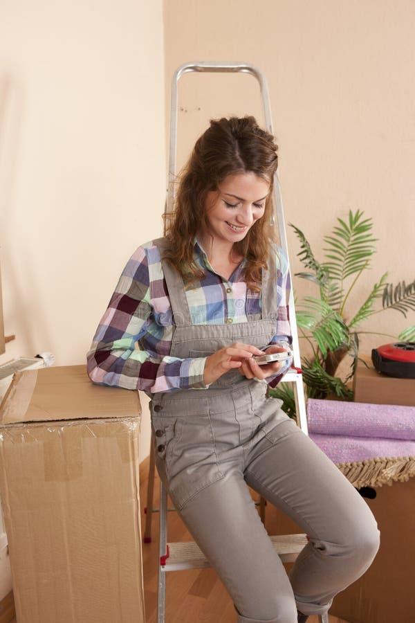 Молодая женщина с умным телефоном во время двигать дома стоковые изображения