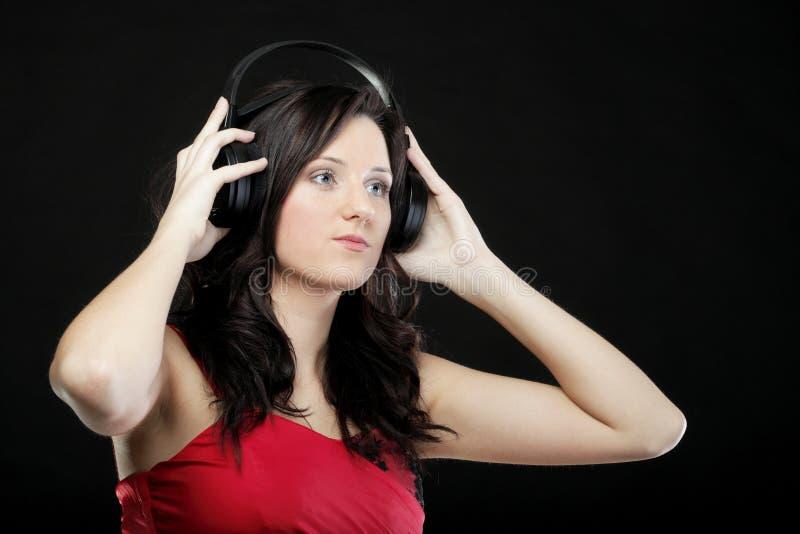 Download Молодая женщина слушая к музыке на шлемофоне Стоковое Изображение - изображение насчитывающей шлемофон, выражение: 33734733