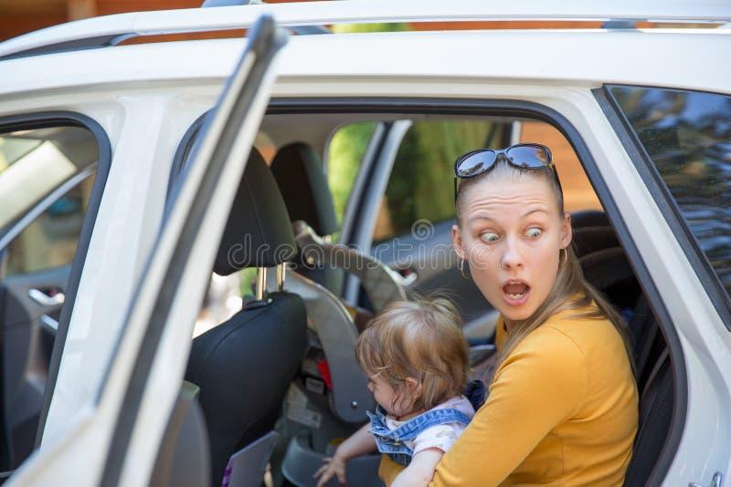 Молодая женщина с удивленным выходом взгляда автомобиль с младенцем стоковые фотографии rf