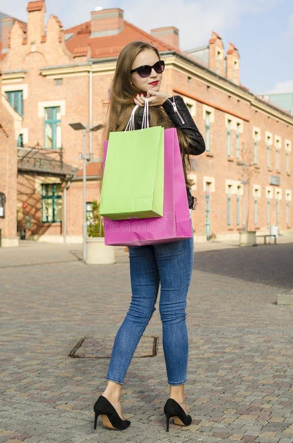 Молодая женщина с цветастыми хозяйственными сумками стоковое фото