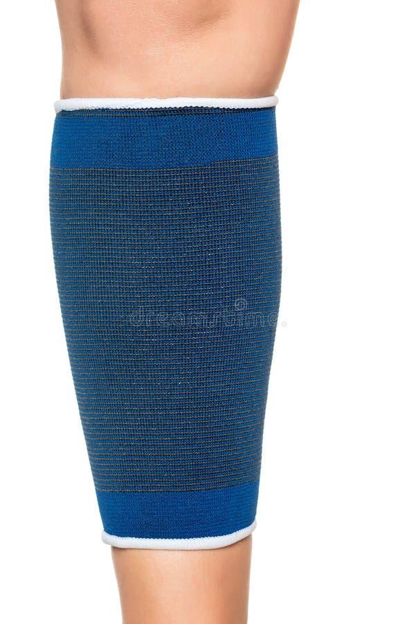 Молодая женщина с эластичной резиновой лентой на ее ноге изолированной на белизне стоковое изображение