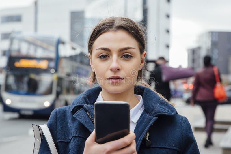 Молодая женщина с Smartphone в городе стоковые изображения