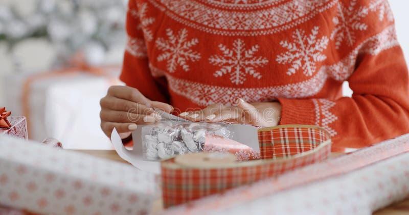 Молодая женщина тщательно оборачивая подарок рождества стоковое изображение