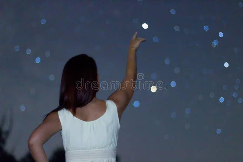 Молодая женщина указывая на defocused звезду Женщина под звездной ночью, женщина указывая к Defocused созвездию Scorpius стоковое изображение
