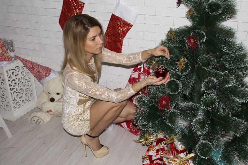 Молодая женщина украшает рождественскую елку стоковые изображения rf