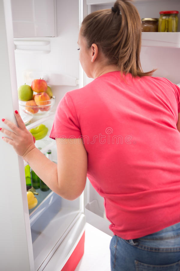 Молодая женщина думает что принять от холодильника стоковая фотография
