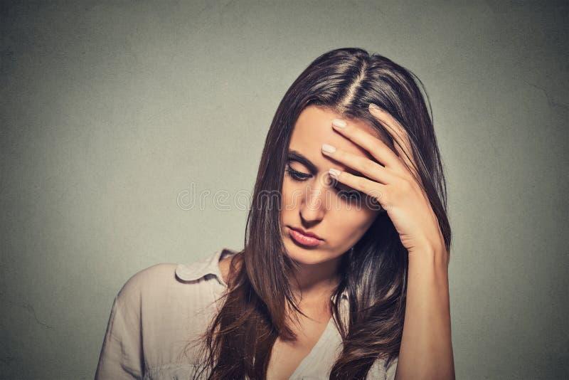 Молодая женщина усиленная портретом унылая смотря вниз стоковые изображения