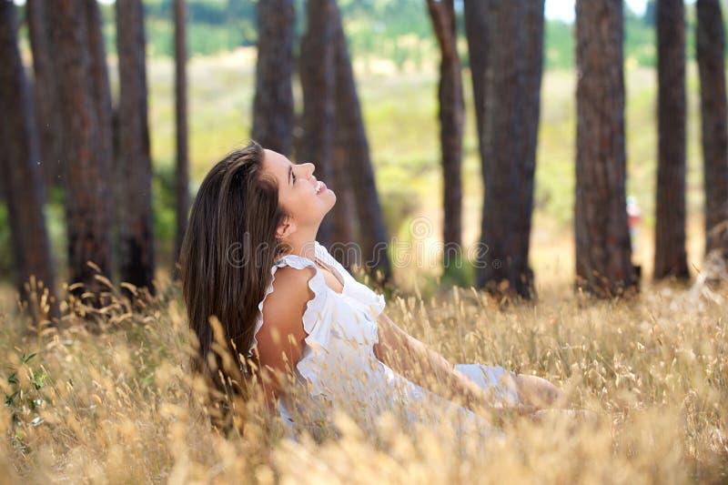 Молодая женщина усмехаясь в луге сельской местности стоковое изображение rf