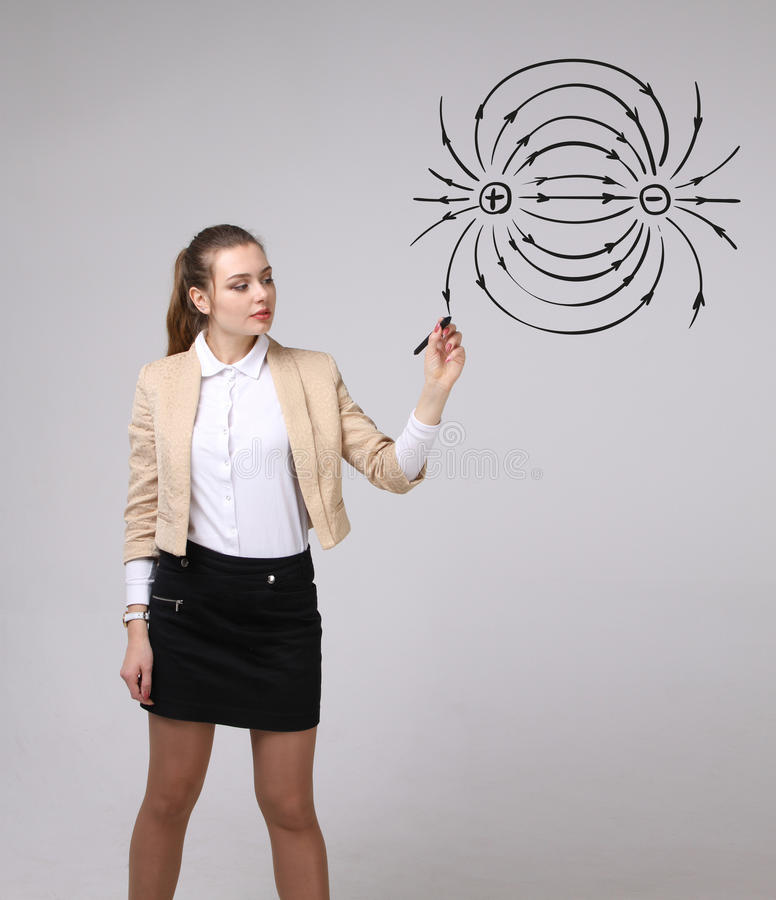 Молодая женщина, учитель физики рисует диаграмму электрического поля стоковое фото