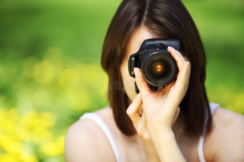 Молодая женщина фотографируя в парке лета стоковые изображения rf