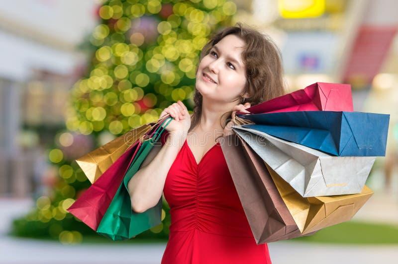 Молодая женщина ходя по магазинам подарки для рождества в магазине и носить много сумок стоковые фотографии rf