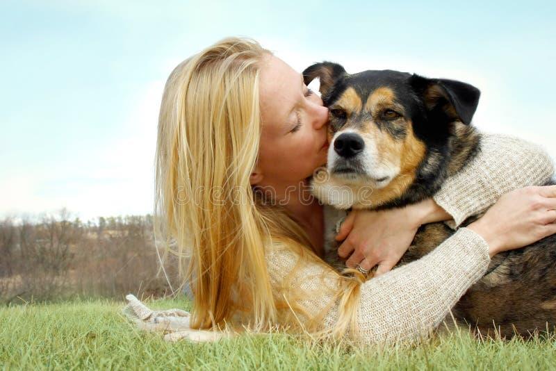 Молодая женщина целуя собаку немецкой овчарки снаружи стоковое фото