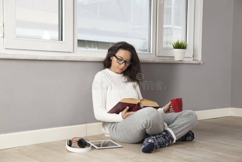 Молодая женщина читая книгу дома стоковое фото