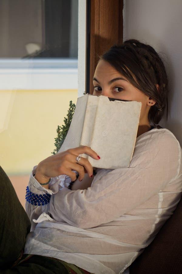 Молодая женщина читая книгу перед окном в ее уютном ho стоковая фотография rf