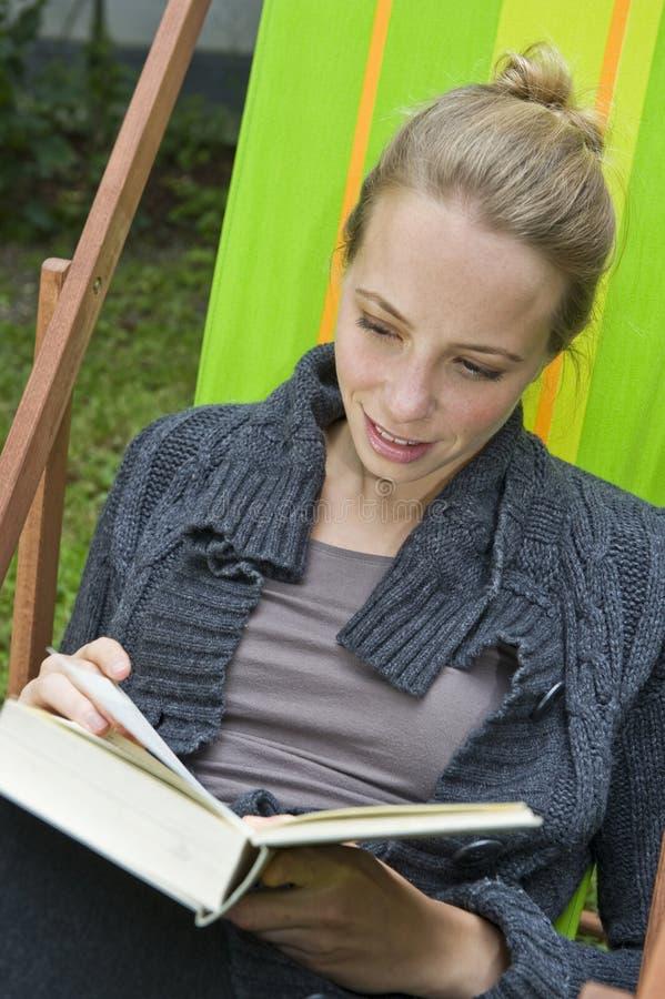 Молодая женщина читая роман стоковые фото