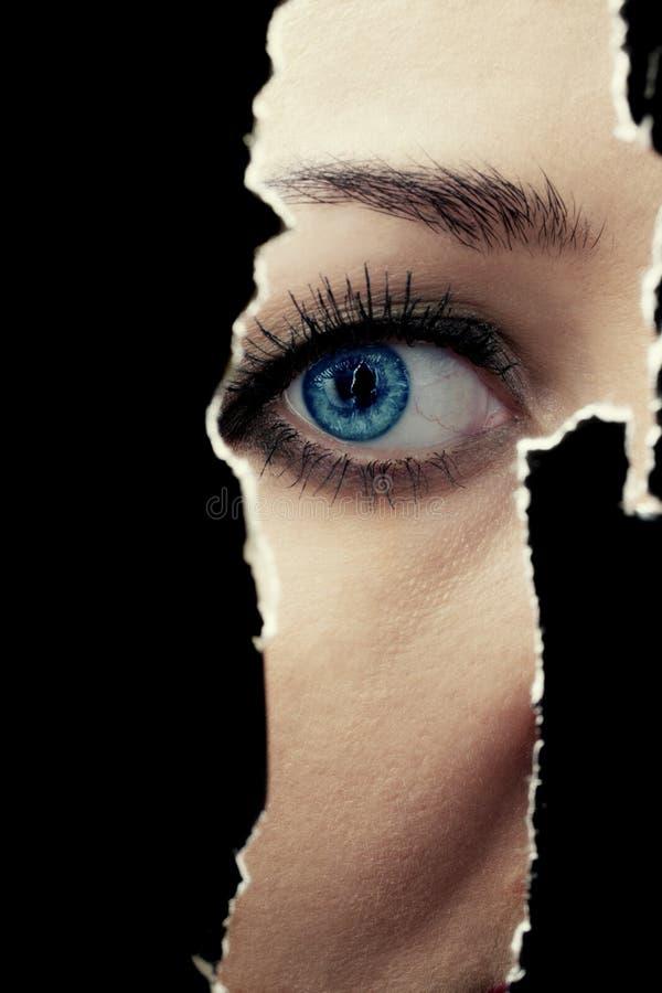 Молодая женщина шпионя через отверстие в стене стоковое изображение rf