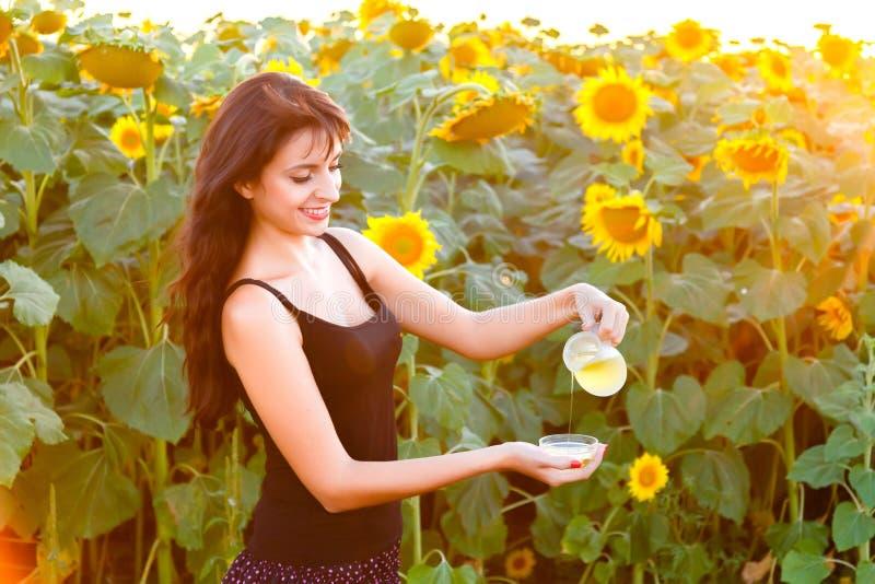 Молодая женщина льет подсолнечное масло от кувшина в шар стоковое изображение
